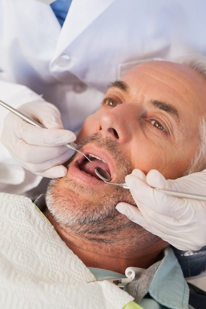 Dentist examining a patients teeth in the dentists chair at the dental practice tepper